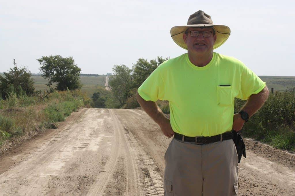 Mike Snyder standing on a long dirt road
