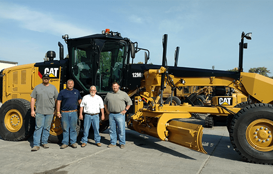 4 men in front of large Cat truck